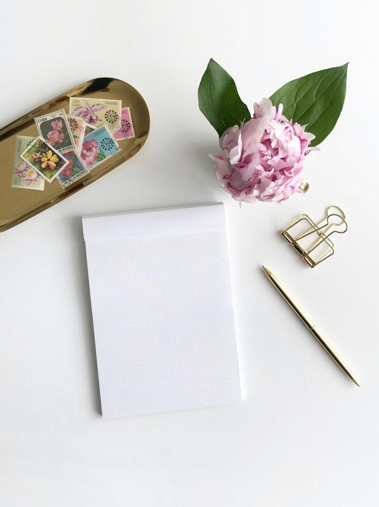 calepin, stylos, fleurs et timbre sur une table. Paris en Noces. Wedding planner Paris