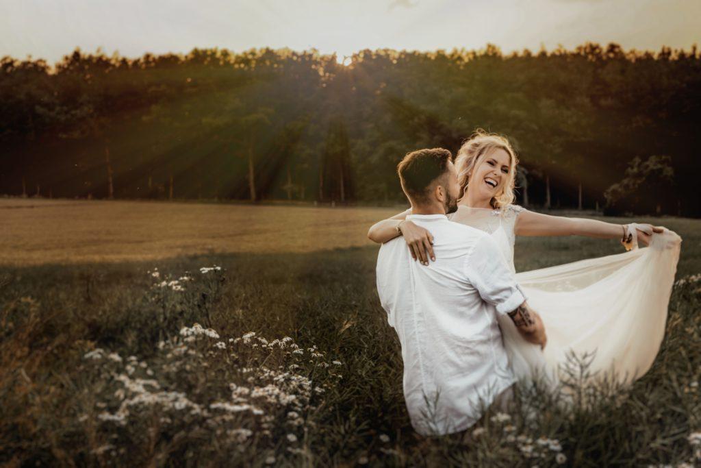 Couple en tenue de mariage dans un champs. Organisation de A à Z. Wedding planner Ile de France. Paris en Noces