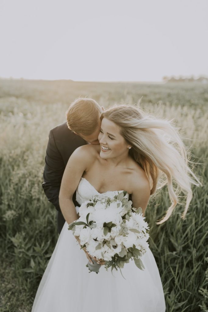 Couple s'enlaçant, avec la mariée avec un sourire rayonnant, kit de survie de la mariée. Paris en Noces. Wedding planner en île de France