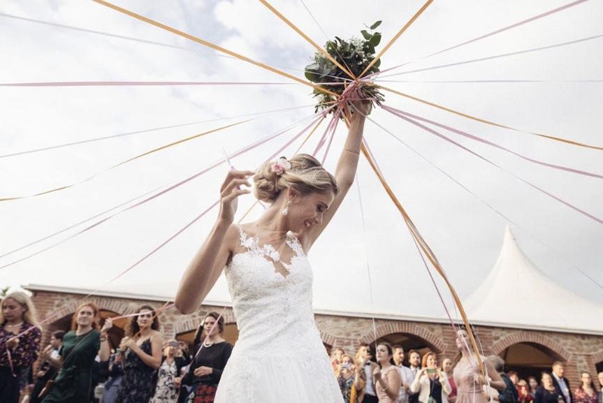 Mariée souriante, ciseaux en mains, prête à couper les rubans accrochés à son bouquet de mariage. lancer de bouquet.Paris en Noces.Wedding planner en île de France.
