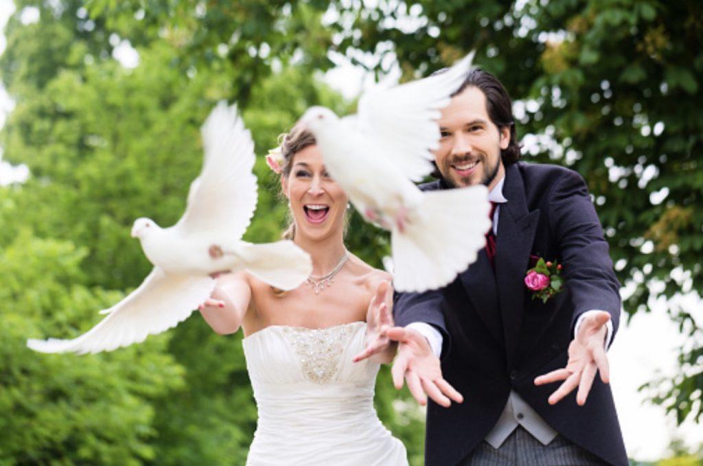 Jeunes mariés qui lâchent 2 colombes.  sortie de cérémonie. Paris en noces. Wedding planner en île de France