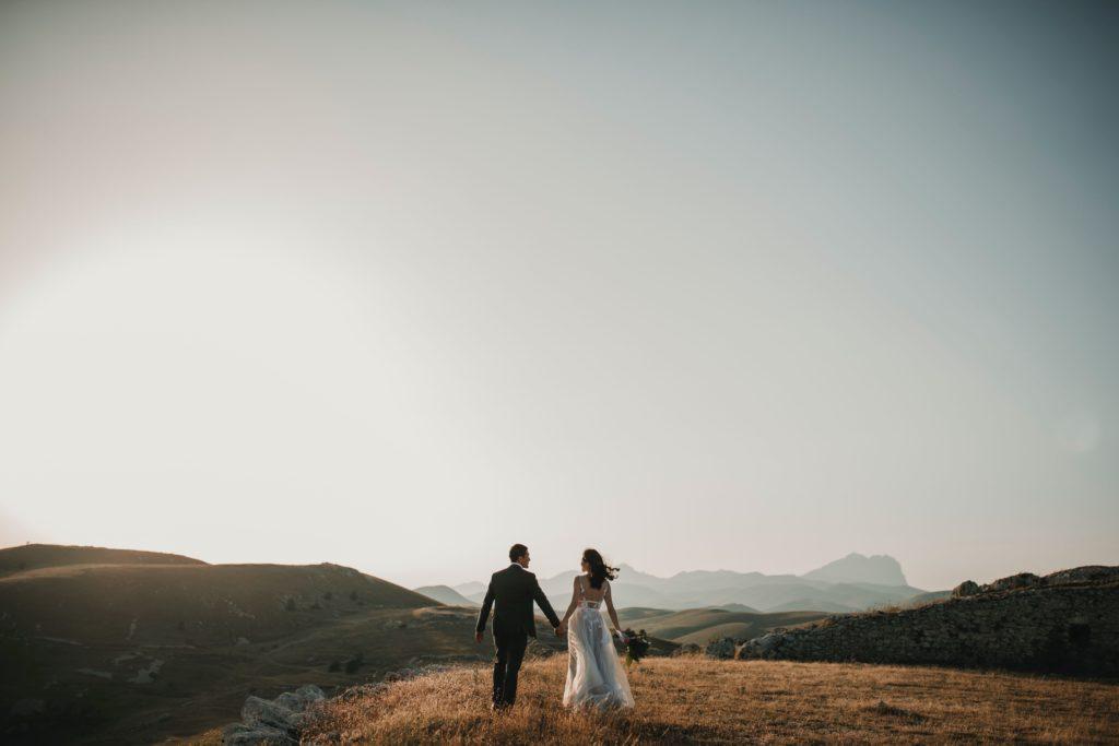 Mariés qui se tiennent la main et paysage de montagne. coaching organisation de mariage. Paris en noces. Wedding planner en ile de france