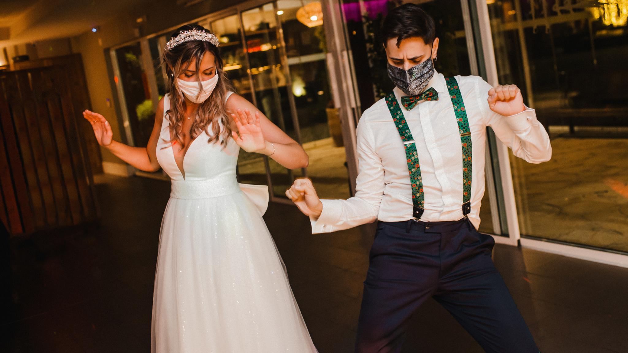 Mariés avec un masque qui dance sur la piste. Mariage et covid. Wedding planner ile de France. Paris en Noces